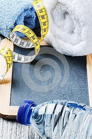 Fitness background with water bottle and towels