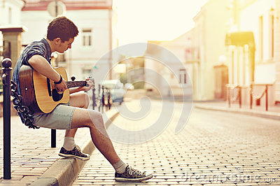 Young man playing on acoustic guitar - outdoor