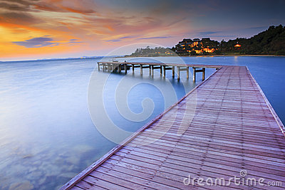 Wood bridge piers with nobody and smoothy sea water against beau