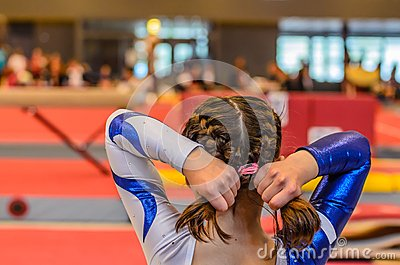Young gymnast girl fixing hair before appearance