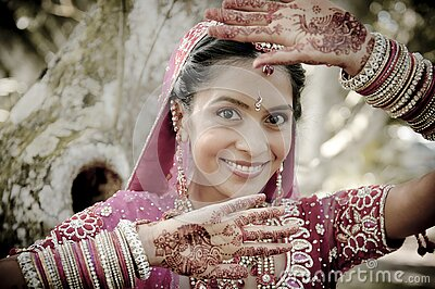 Young beautiful Indian Hindu bride standing under tree with painted hands raised