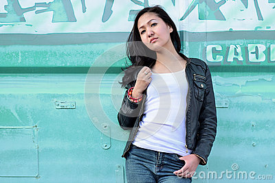Sensuality woman in white T-shirt, black leather jacket, blue jeans and black long hair in the background blue urban iron
