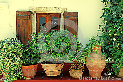 Window with wood shutters and flower pots (Crete, Greece)
