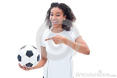 Pretty football fan in white holding ball and pointing to it