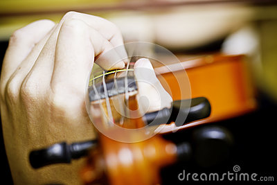 Hands holding strings on a violin