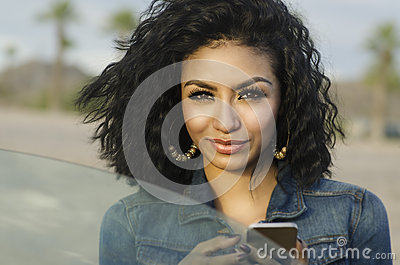 Pretty young woman beside her car making phone call