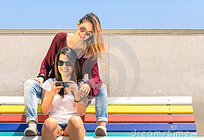 Best friends girlfriends enjoying time together outdoors with smartphone