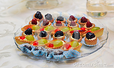 Set of tasty mini cakes with raspberries, blackberries, cranberries, blueberries and grapes on white table. Wedding decoration