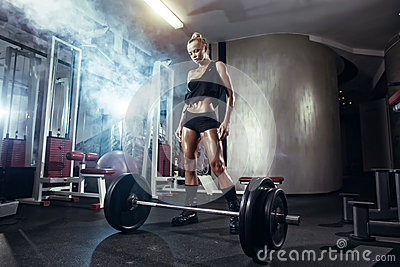 Fitness woman prepares for exercising with barbell in gym