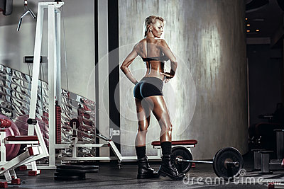 Fitness blonde girl prepares for exercising with barbell in gym