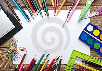 School stationery frame on wooden background: paper, pencil, brush, scissors, folders, abacus,