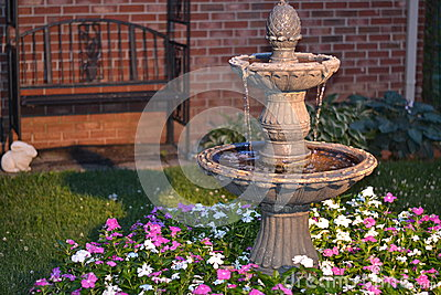 Decorative home water fountain in a bed of flowers
