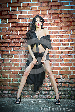 Charming young brunette woman in black and high heels staying near a red brick wall