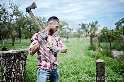 Athletic man lumberjack cutting logs for firewood with axe