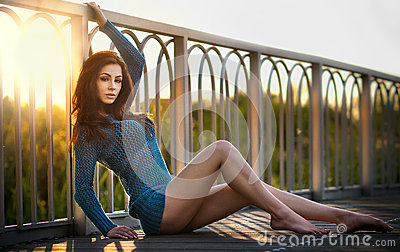 Fashionable redhead in blue blouse and long legs laying down on a wooden bridge. Beautiful girl with long hair posing, outdoors
