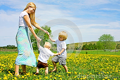 Mother and Children Playing and Dancing Outside in Flower Meadow