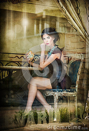 Fashionable attractive young woman in black dress sitting in restaurant, beyond the window. Beautiful brunette posing in window