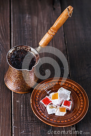 Turkish coffee and Turkish Delight over dark wooden background