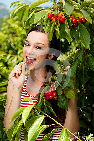 Beautiful young woman eats cherry on plantation