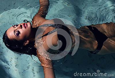 Sexy girl with dark hair posing at swimming pool at night