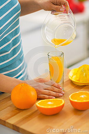 Closeup on young woman pouring fresh orange juice