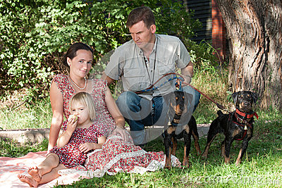 The man with two dogs protects the woman with the child
