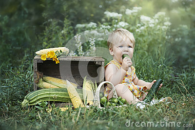 Little girl eating self grown cucumber