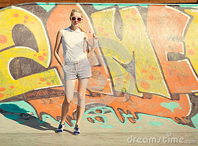 Beautiful young blond woman in sunglasses and a lollipop stands on graffiti background. Toned in warm colors