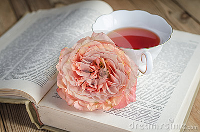 Cup of tea, a book and a rose