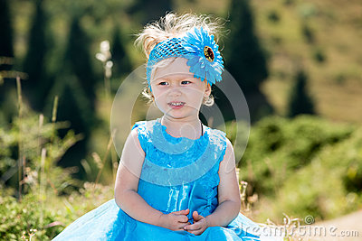 Adorable little child girl on grass on meadow. Summer green nature background.