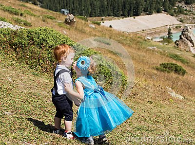 Baby boy and adorable child girl on grass. Summer green nature background.