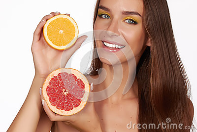 Beautiful brunette woman with citrus on a white background, healthy food, tasty food, organic diet, smile healthy