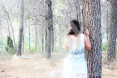 Surreal photo of young woman standing in forest. natural light. dreamy concept.