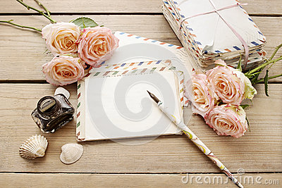 Vintage letters, roses and bottle of ink on wooden table.