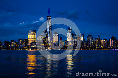 New York City Manhattan downtown skyline with skyscrapers illuminated over Hudson River panorama