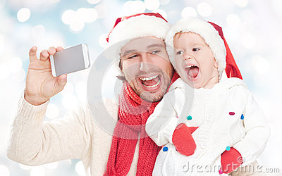 Selfe  in winter. happy family dad playing with daughter and photographed on  mobile phone