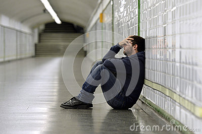 Young sick man lost suffering depression sitting on ground street subway tunnel