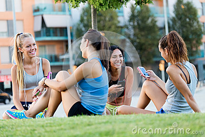 Running girls having fun in the park with mobile phone.