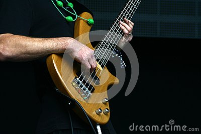 Bass player hands with five string bass guitar