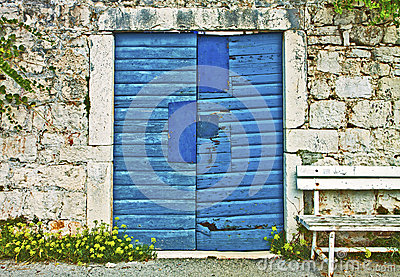 Stone wall, vintage blue gate and wooden bench
