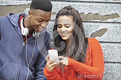 Teenage Couple Sharing Text Message On Mobile Phone