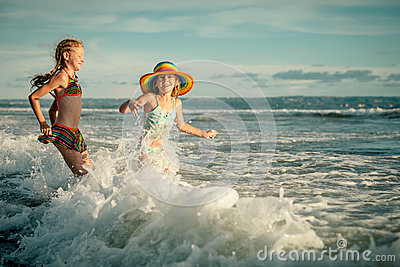 Two sisters splashing on the beach