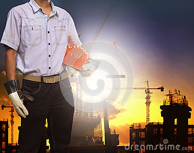 Engineer man working with white safety helmet against crane and building construction site use for civil engineering and construc