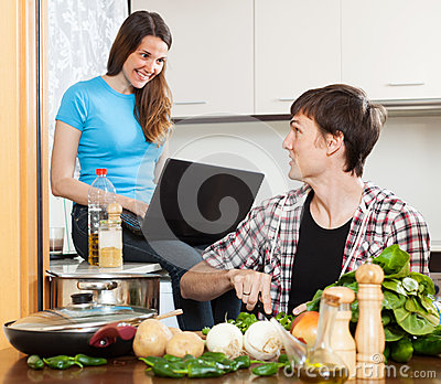 Man cooking food while girlfriend looking at laptop