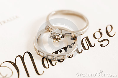 Sepia vintage retro style wedding and diamond engagement rings on marriage certificate