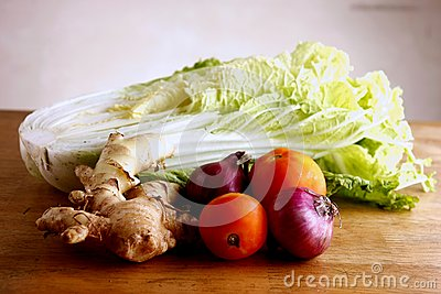 Garlic, onion, ginger, tomato and cabbage on a chopping board