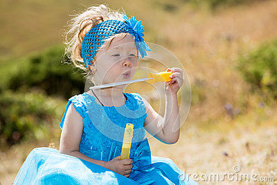 Adorable little child girl with bubble blower on grass on meadow. Summer green nature .
