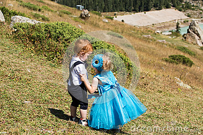 Baby boy and adorable child girl kissing on grass. Summer green nature .