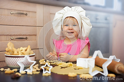 Little child chief cooking cookies in the kitchen