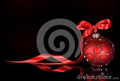 Christmas background with red ornament and ribbon on a black background